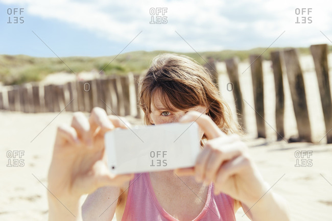 Portrait of woman photographing with her smartphone on the beach
