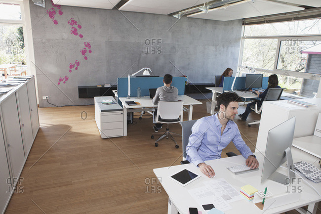 Four colleagues working in modern open space office