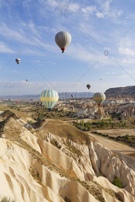 Hot air balloons hovering over tuff rock formations at Goereme National Park, Turkey