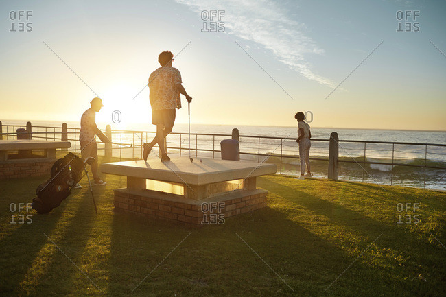 Friends playing urban golf at the coast