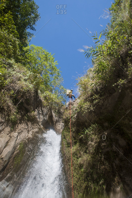 A man abseils down a waterfall in Nepal near the Tibetan border