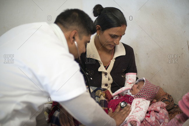 Beni district, Nepal - October 31, 2013: A general practitioner checks a patient's baby with a stethoscope in a rural hospital
