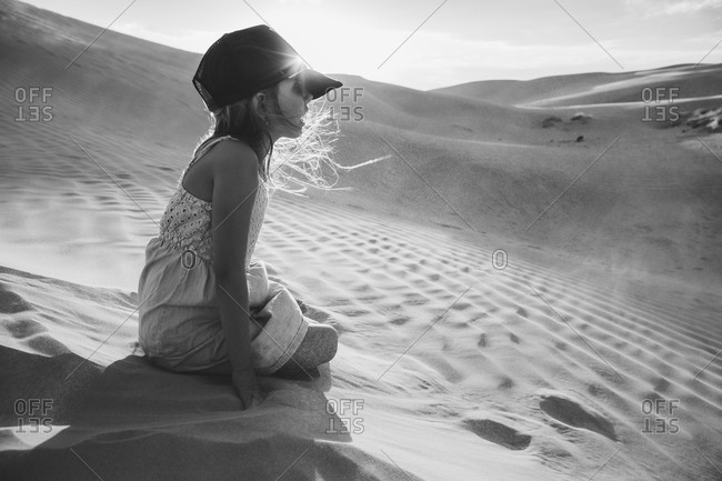 Girl kneeling in a desert