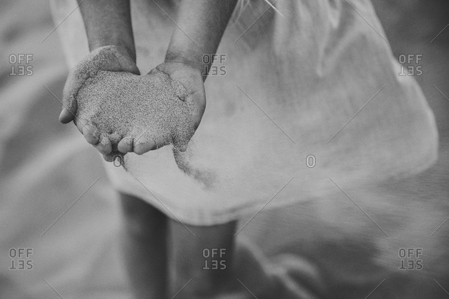 Girl holding a handful of sand