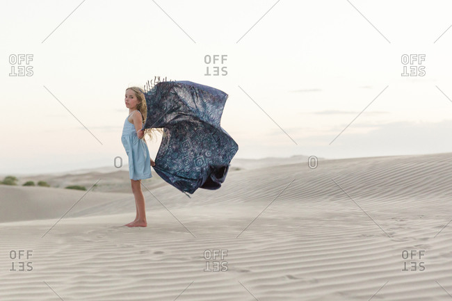Girl posing with a blanket in a windy desert