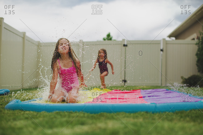 Girl sliding on an inflatable water slide