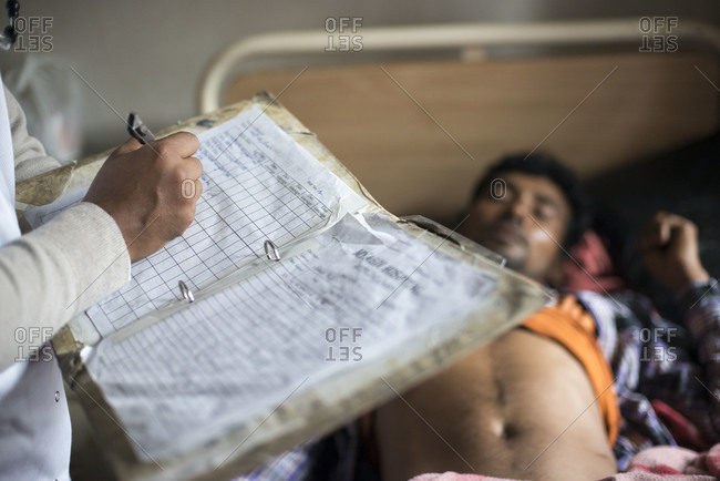 A doctor in a rural hospital in Nepal takes notes while making his rounds in the ward