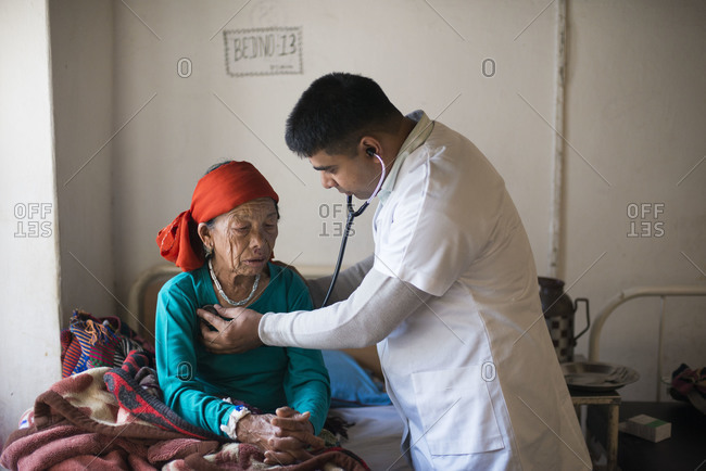 A doctor examines an old woman with a stethoscope in a rural hospital in Nepal