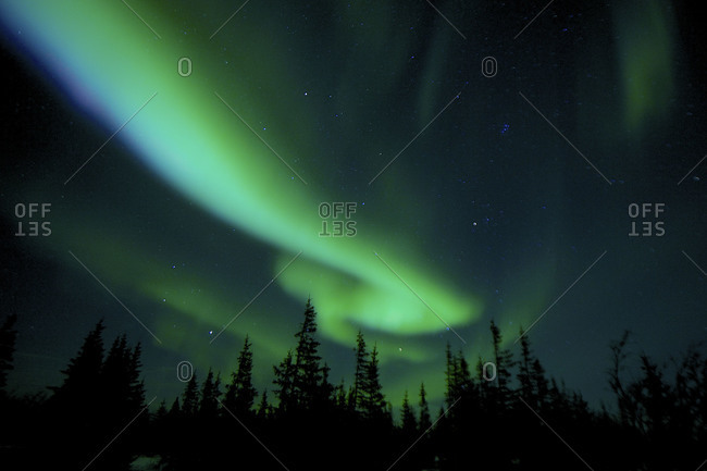 A northern light beam moves across the sky