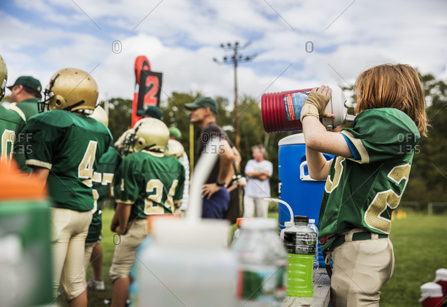 Red-haired football player drinking from water cooler
