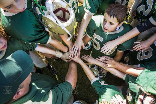 Youth football team and coach touch hands in pre-game huddle