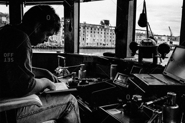New York City Harbor - Circa - 2000: Captain reading in a cabin of a tugboat in New York, City