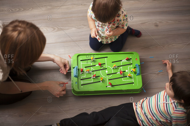 Woman playing mini soccer with two young boys