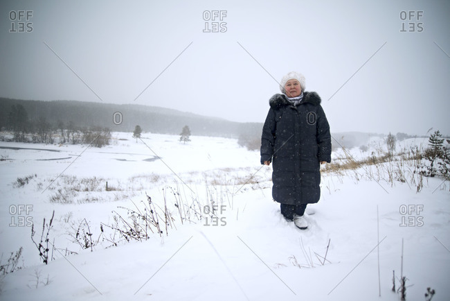 Woman in warm clothing posing in winter landscape