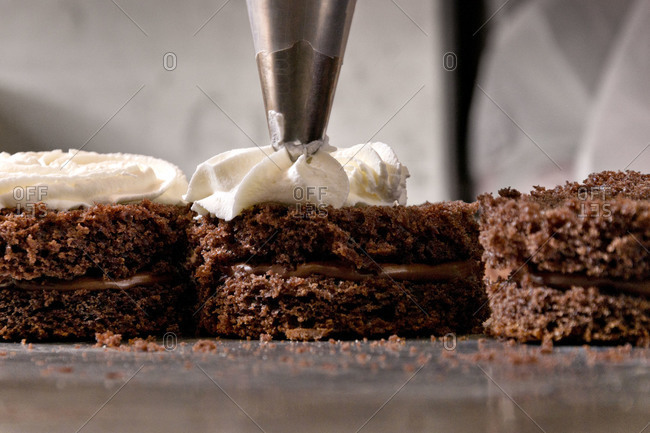 Decorating chocolate mini cakes on commercial kitchen
