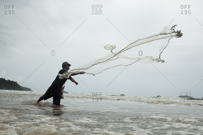 Koh Chang; Southeast Asia; Thailand - August 22, 2013: Side view of man casting a fishing net on a beach, Koh Chand district
