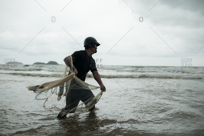 Koh Chang, Thailand - August 22, 2013: Side view of man casting a fishing net on a beach, Koh Chand district