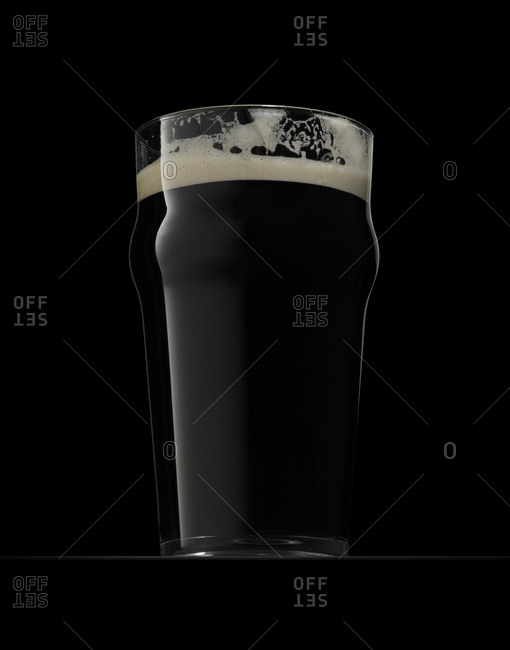 Glass of dry stout on black background