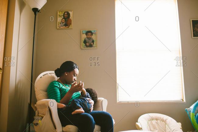 Mother breastfeeding her baby in nursery chair