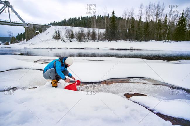 Man gathering river water near a bridge