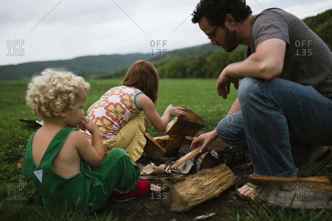 Father and children setting up a campfire