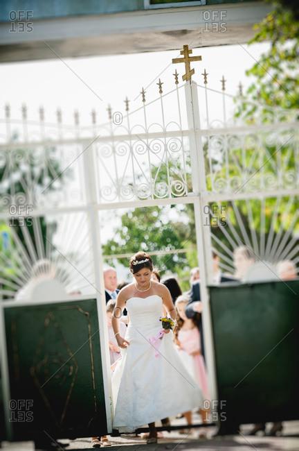 A bride walks through the gate of a church