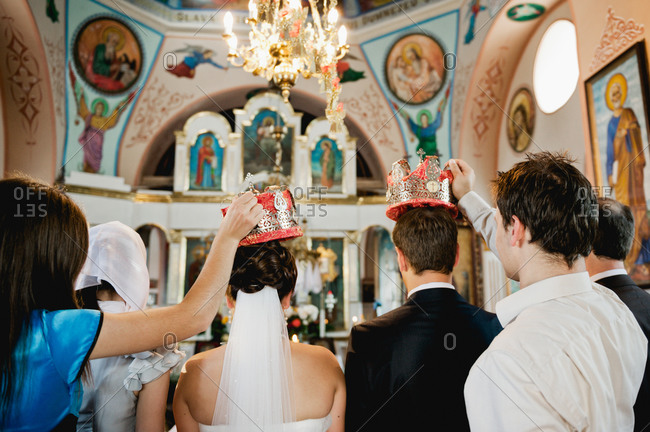 Bride and groom with crowns held over their heads during wedding ceremony