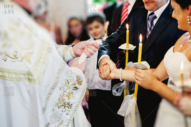 Priest about to bind hands of wedding couple