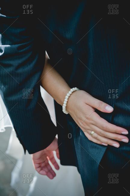 Bride's hand on groom's waist