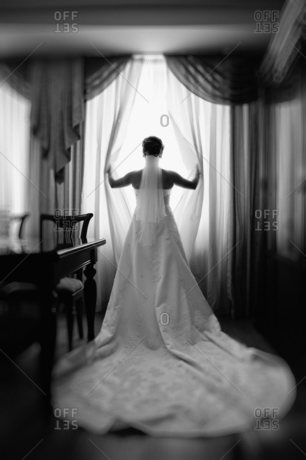 Bride opening curtains to look out window