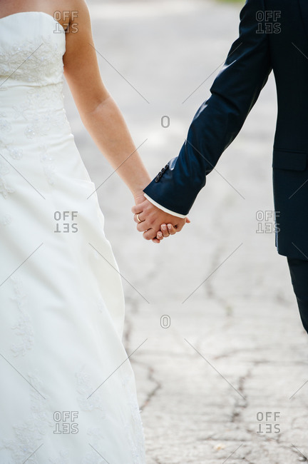 Newlyweds walking hand-in-hand