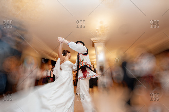 Bride dancing with man in traditional clothing