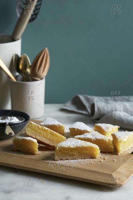 Sprinkled lemon bars on a cutting board