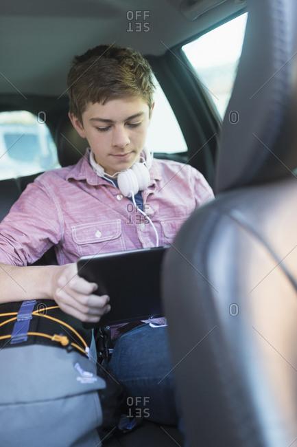 Teenage boy using digital tablet in car
