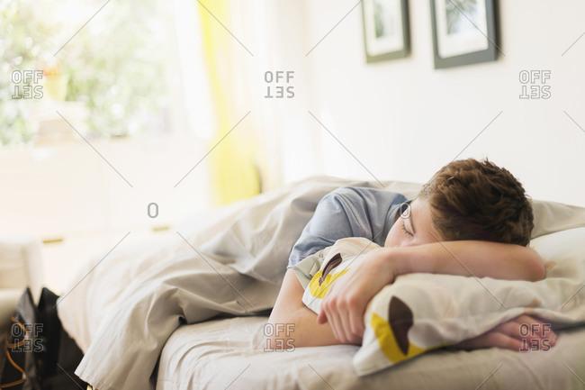 Teenage boy sleeping in bed