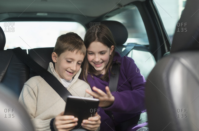 Boy and girl using digital tablet in car