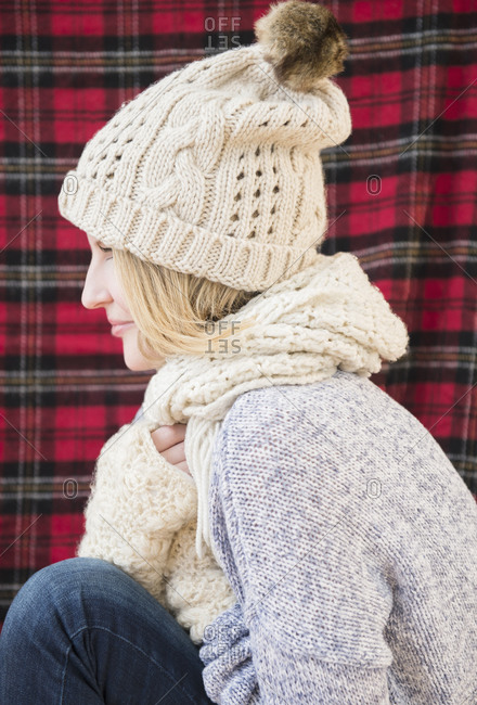 Profile of woman wearing knit hat and scarf