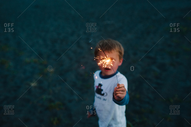 Boy playing with sparkler - Offset