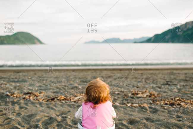 Rear view of little girl watching the water