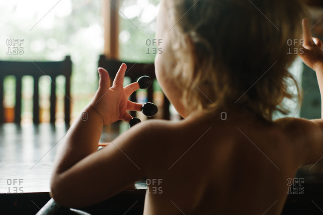 Toddler with olives on fingertips