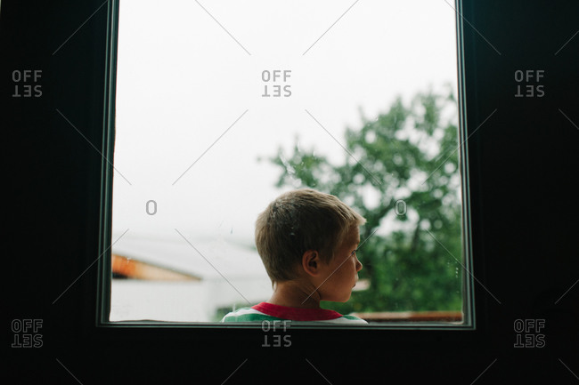 Boy out window looking to side