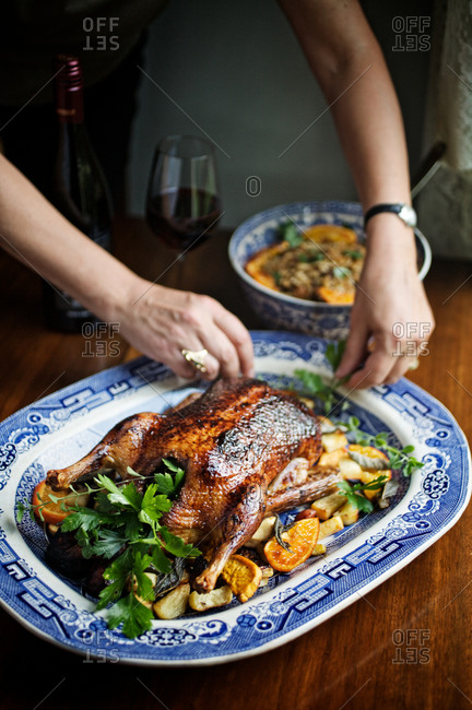 Woman arranging classic roasted chicken with side dish