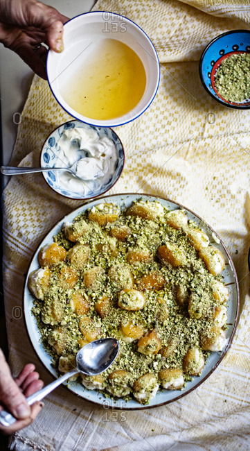 Cream stuffed dry apricots with chopped pistachio, drizzled with sugar syrup