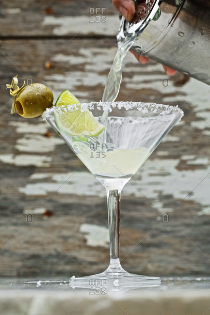 Person pouring margarita cocktail into a rimmed glass