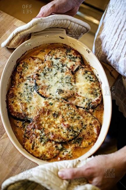 Person holding a dish of eggplant gratin