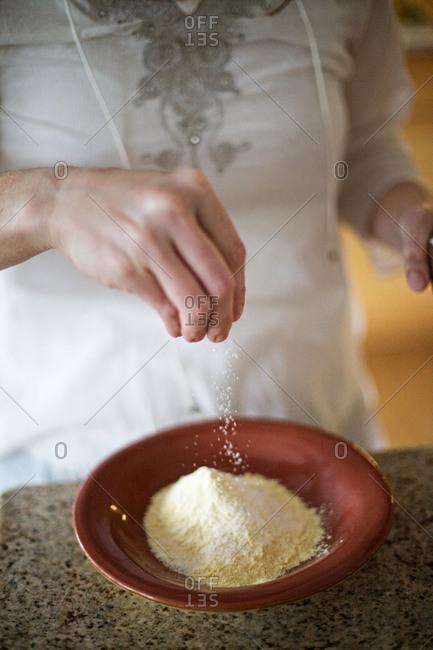 Person adding baking powder to cornflour