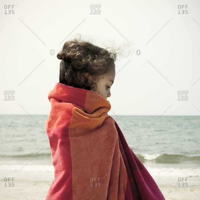 Girl on beach wrapped in towel