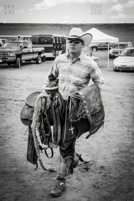 Wagon Mound, New Mexico, USA - September 7, 2009: A cowboy carries saddle