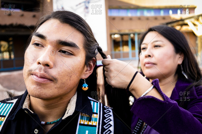 Albuquerque, New Mexico, USA - November 18, 2011:Native American mother braids her son's hair into traditional pigtails