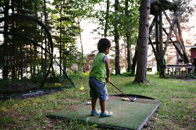 Boy playing miniature golf